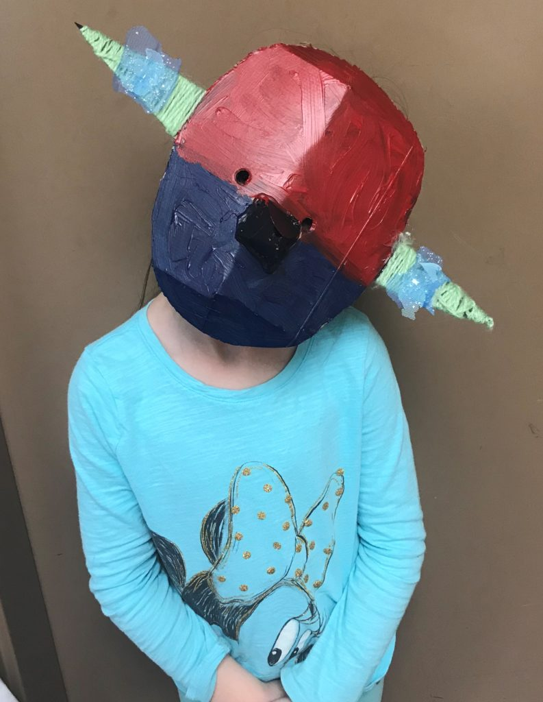 Child wearing a mask made from cereal boxes.